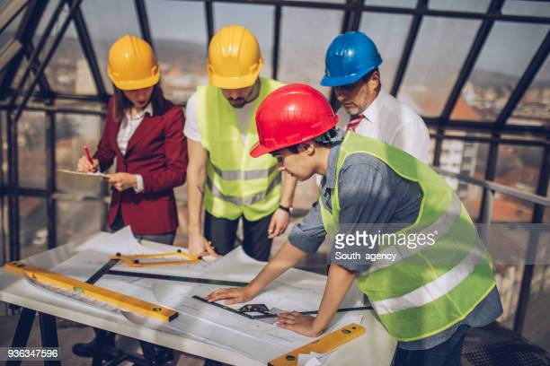 Engineers looking at blueprints at construction site