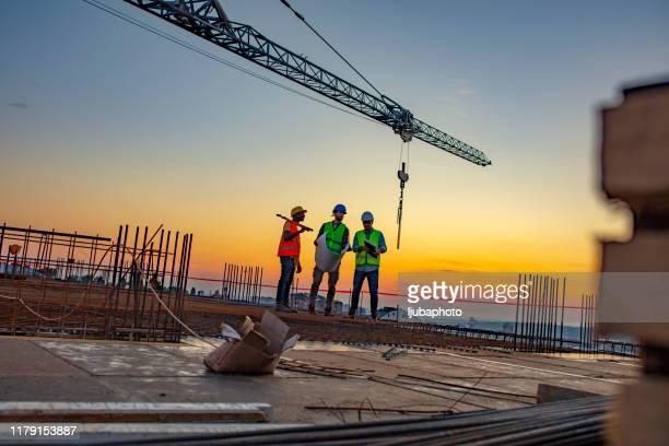 ingegneri che guardano i progetti in cantiere - industria edile foto e immagini stock