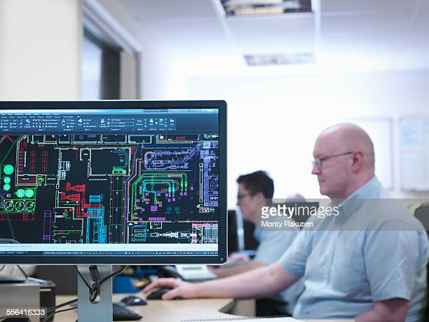 Engineers looking at CAD designs in office of engineering factory