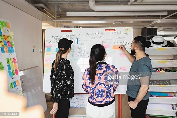 Engineers looking at whiteboard in creative office