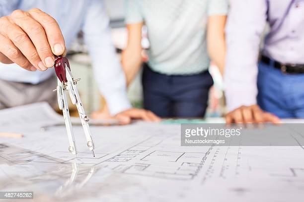 Engineers Measuring Blueprint With Drawing Compass At Desk