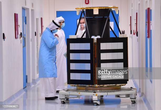 Engineers observe a KhalifaSat model at the Mohammed Bin Rashid Space Centre , in the Gulf emirate of Dubai on July 5, 2020. - The oil-rich United...