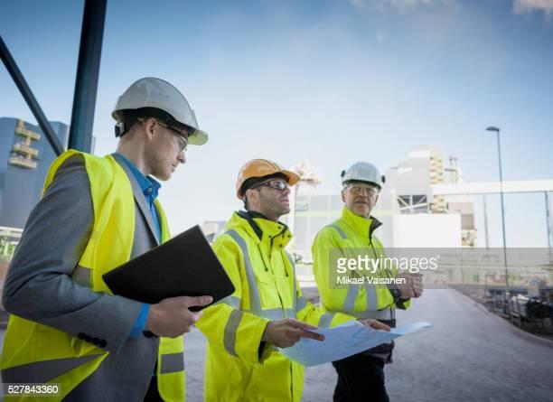 engineers on modern power station construction site - abbigliamento da lavoro foto e immagini stock