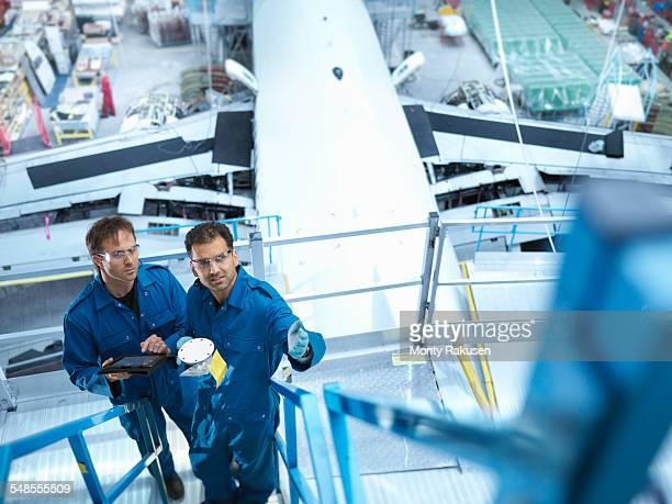 Engineers on scaffolding in aircraft maintenance factory