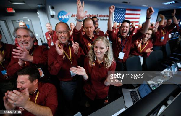 NASA engineers on the flight team celebrate the InSight spacecraft's successfull landing on the planet Mars from the Mission Support area in the...