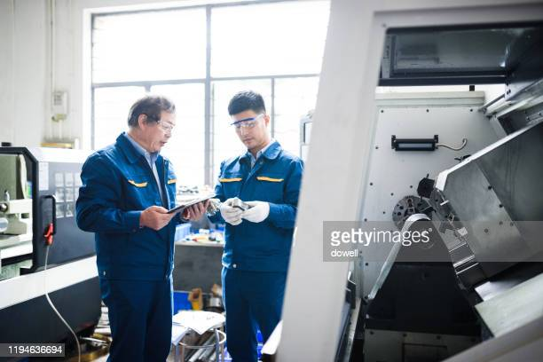 engineers operating cnc lathes with digital tablet in factory - technician stock pictures, royalty-free photos & images