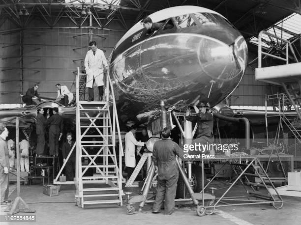 Engineers oversee the inspection of a British Overseas Airways Corporation de Havilland DH106 Comet 1 passenger jet airliner in its hanger at...