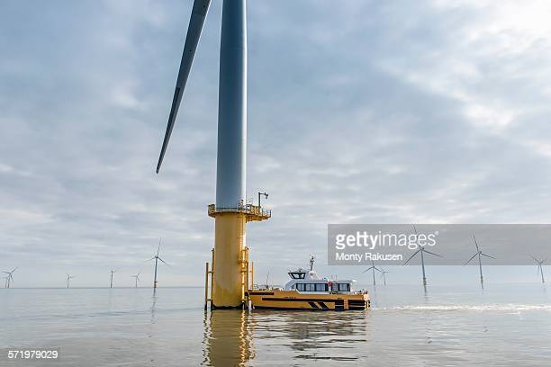 engineers preparing to climb wind turbine from boat at offshore windfarm - besatzung stock-fotos und bilder