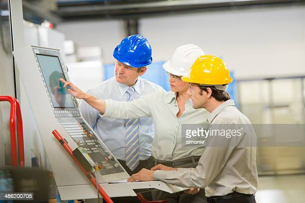 engineers programming a cnc machine - mechatronics stock pictures, royalty-free photos & images