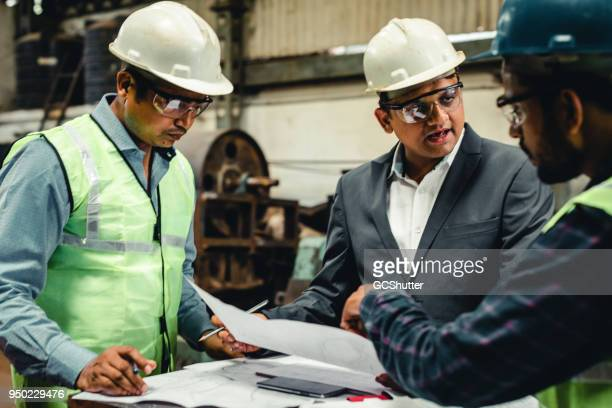 engineers proposing ideas to improve the factory. - hard hat stock pictures, royalty-free photos & images