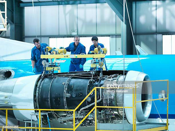 Engineers removing jet engine from aircraft in aircraft maintenance factory