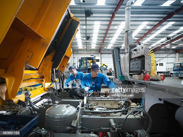 Engineers repairing engine in truck repair factory