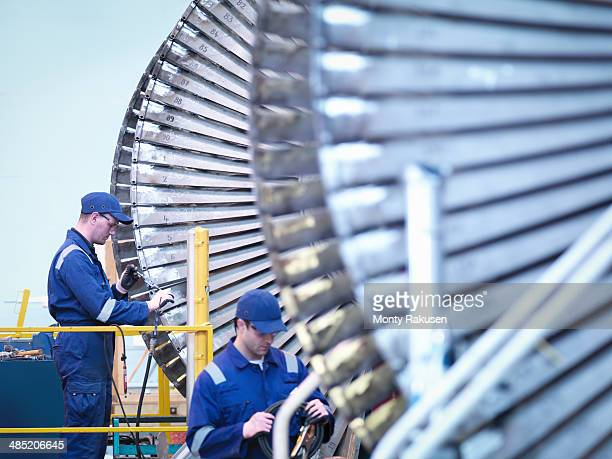 Engineers repairing steam turbine in repair bay in workshop