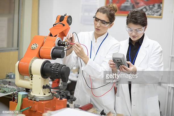 Engineers reparing machine in lab