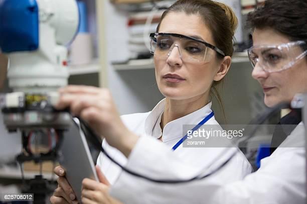 Engineers reparing robotic arm