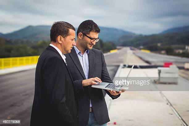 Engineers standing on bridge and looking at laptop