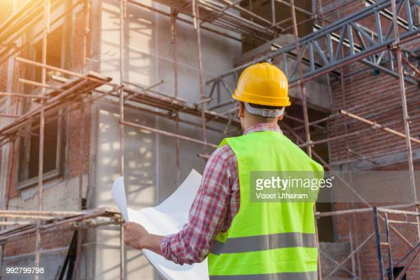 Engineers standing writing on clipboard at construction site on building site