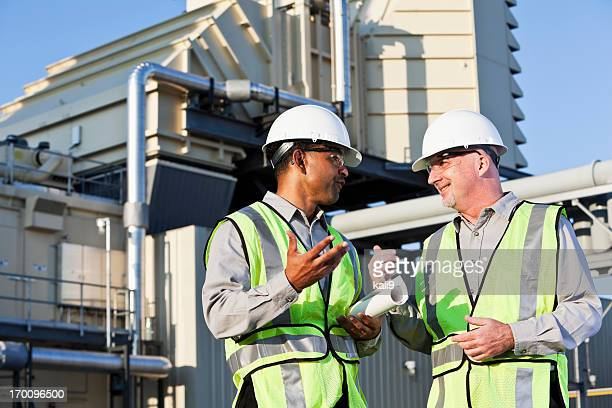 Engineers talking near power generator