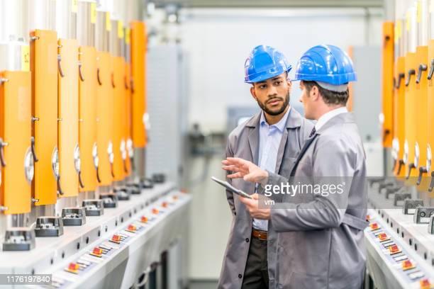 ingenieure sprechen bei der inspektion von maschinen - ingenieurwesen stock-fotos und bilder