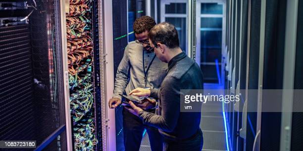 it engineers using a digital tablet in the server room of a data center - data center stock pictures, royalty-free photos & images