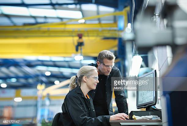 Engineers using computer to work on plans in engineering factory