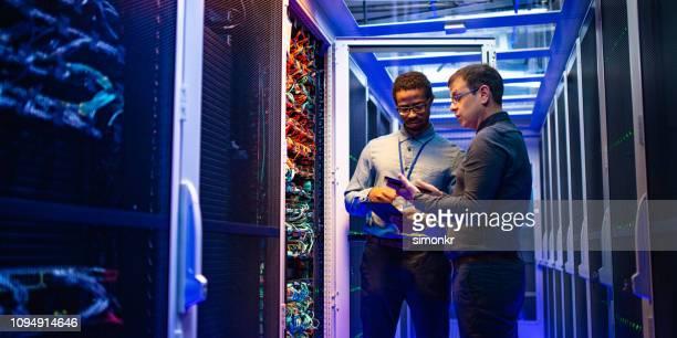 engenheiros it usando digital tablet e smartphone - servidor de rede - fotografias e filmes do acervo