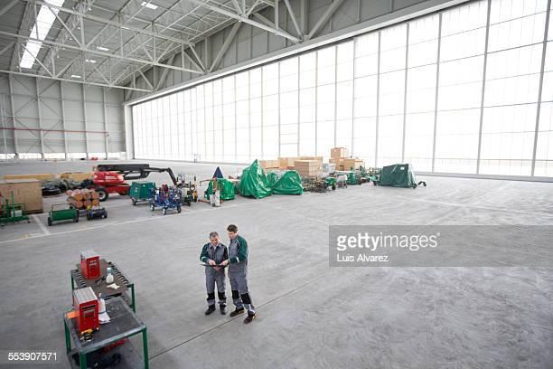 Engineers using digital tablet in hangar