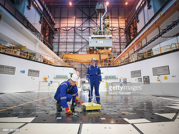 engineers using sensors on pile cap in nuclear power station - nuclear reactor stock pictures, royalty-free photos & images