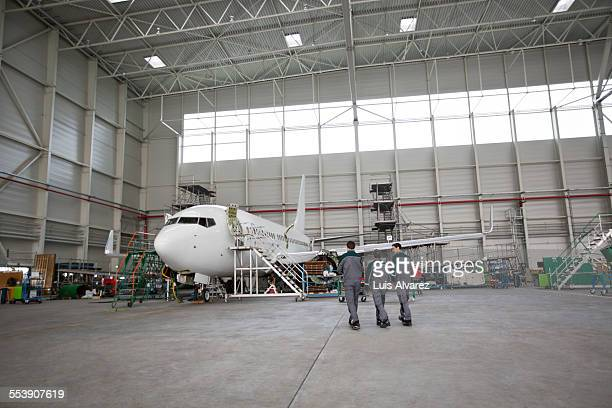 Engineers walking towards airplane in hangar