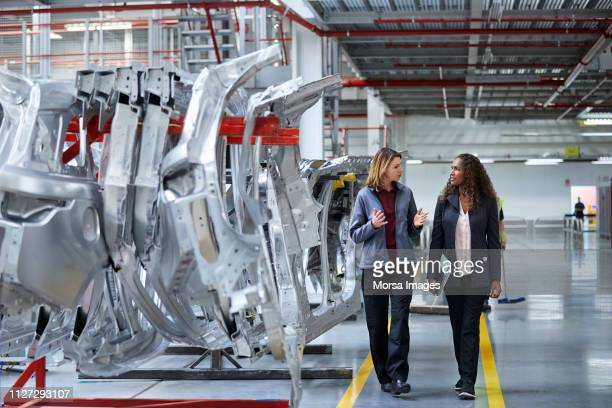 engineers walking while discussing by car chassis - manufacturing stock pictures, royalty-free photos & images