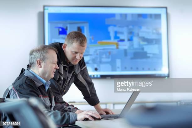 engineers with cad drawing in metal pressing factory - rechnerunterstütztes konstruieren stock-fotos und bilder