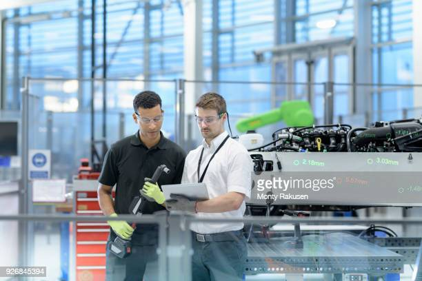 engineers with digital tablet and robot inspecting car in robotics research facility - mechanical engineering stock pictures, royalty-free photos & images