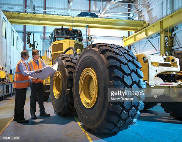 Engineers with engineering drawings inspecting heavy truck