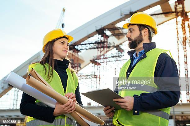 Engineers with hardhats and blueprints on construction site