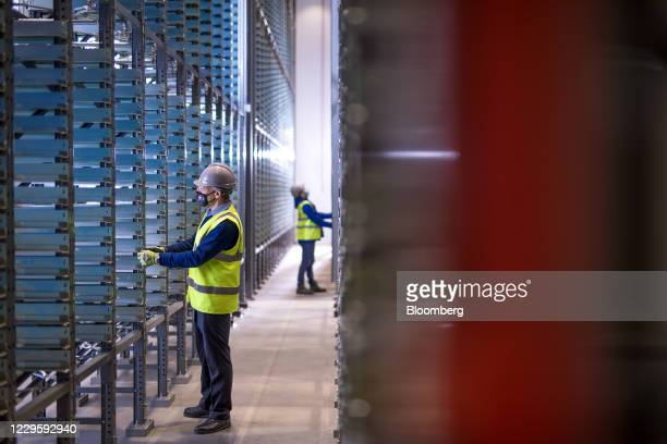 Engineers work amongst racks in the formation ageing area at the U.K. Battery Industrialization Centre in Coventry, U.K. On Monday, Nov. 9, 2020. The...
