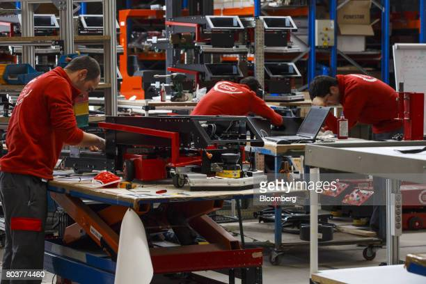 Engineers work on the assembly of 'Easybot' mobile robots also known as an AGV or automated guided vehicle during development and testing inside the...