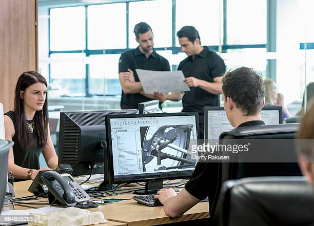 engineers work with cad design imagery in racing car factory - rechnerunterstütztes konstruieren stock-fotos und bilder