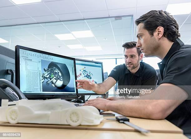 engineers work with cad design imagery in racing car factory - ingenieur stock-fotos und bilder