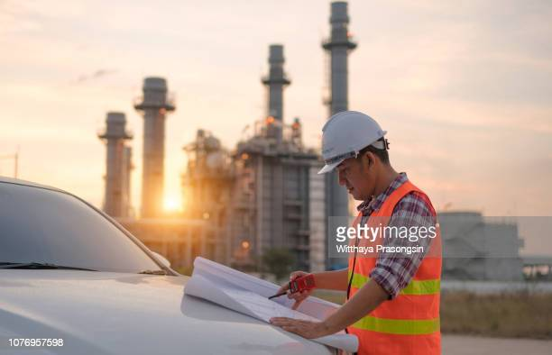 engineers working in the power plant area who are holding blueprint concepts and architectural power plant designs. - torre estrutura construída imagens e fotografias de stock