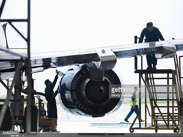 Engineers working on aircraft wing in aircraft maintenance factory