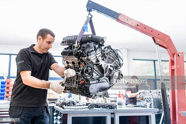 Engineers working on engines in racing car factory