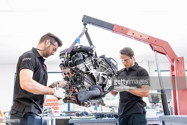 engineers working on engines in racing car factory - 吊り上げる ストックフォトと画像