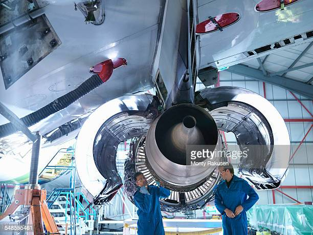 Engineers working on jet engine in aircraft maintenance factory