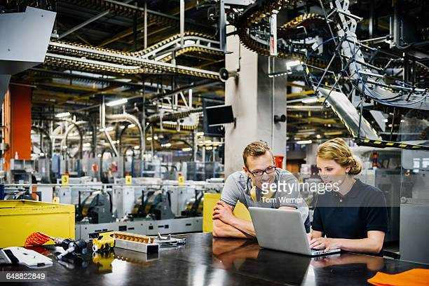 Engineers working on laptop in a large printer