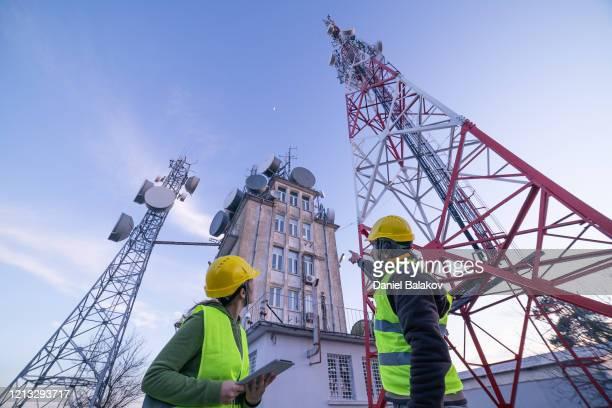 ingenieure, die auf dem feld in der nähe eines telekommunikationsturms arbeiten. teamarbeit. - antenne stock-fotos und bilder