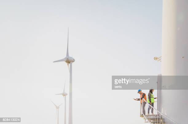 engineers working on wind turbine in wind farm - windmills stock photos and pictures