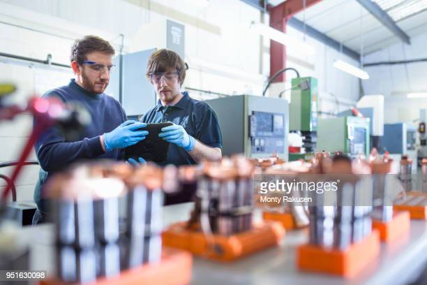 engineers working with electrodes for electrical discharge machine in precision engineering factory - monty rakusen stock photos and pictures