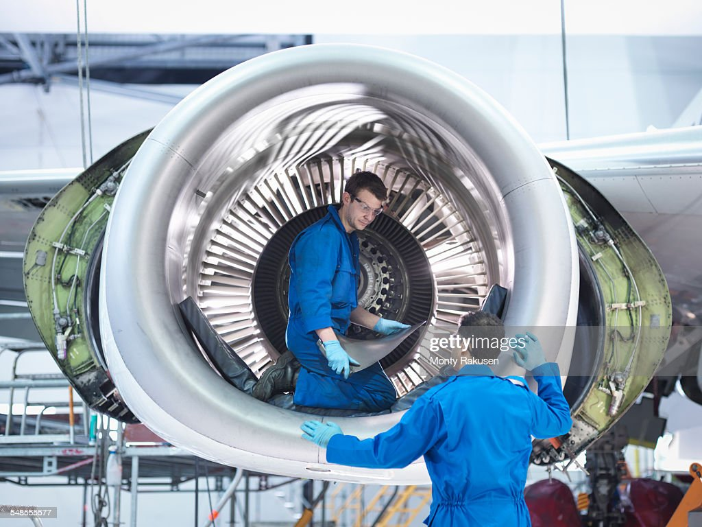 Engineers working with jet engine turbine blade in aircraft maintenance factory : ストックフォト