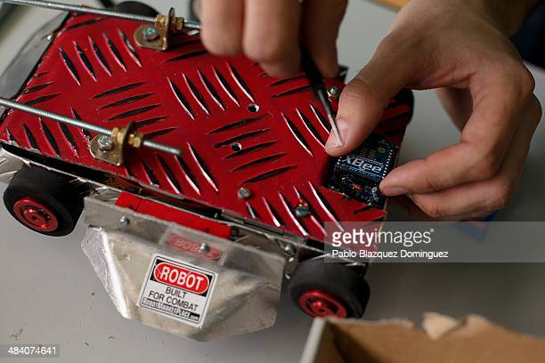 Enginnering student Carlos Hucha works on his robot 'Troncomovil' before a sumo robots combat during the Cybertech robotics competition at the the...