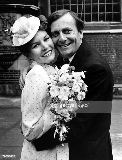England, 17th June 1979, Australian comic actor Barry Humphries hugs his new bride, artist Diane Millstead after their marriage at London's...